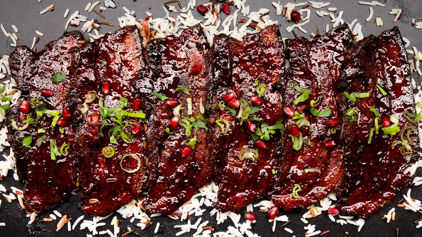 mediterranean-style pomegranate-glazed pork belly strips
