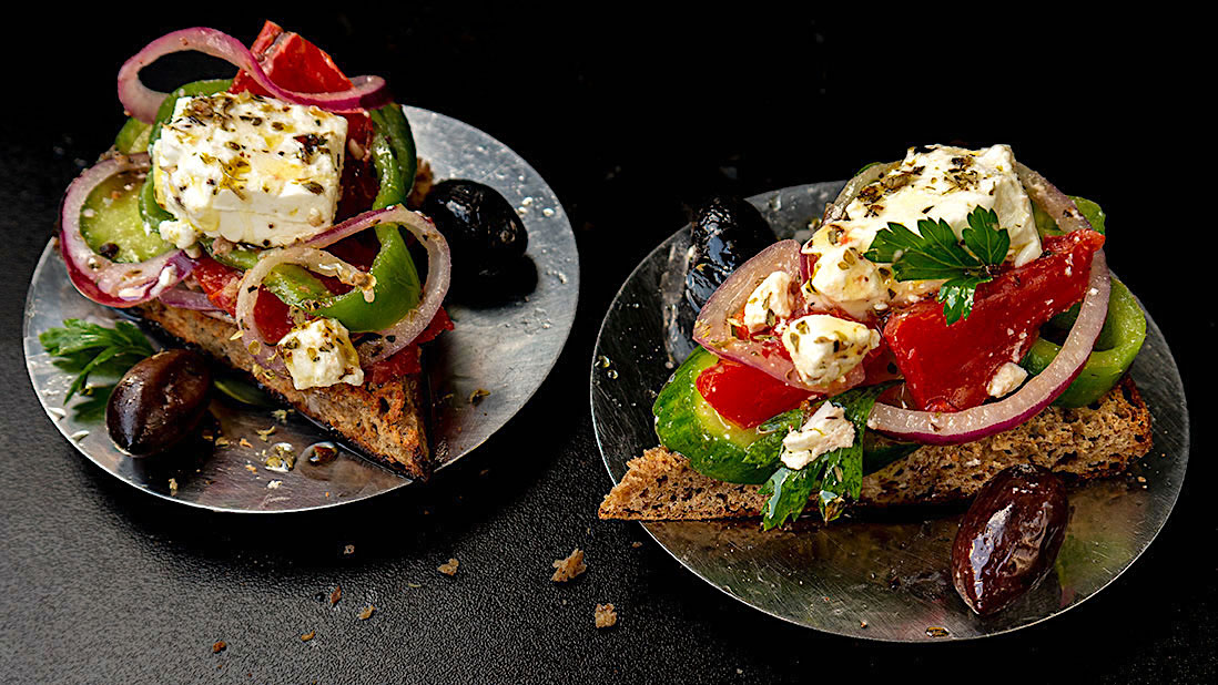 "rustic greek ""choriatiki"" salad slices on flatbread rusks"